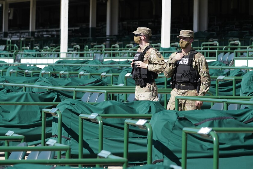 Military Police, working as security, stand in empty stands before the 146th running of the Kentucky Derby at Churchill Downs, Saturday, Sept. 5, 2020, in Louisville, Ky. (AP Photo/Mark Humphrey)