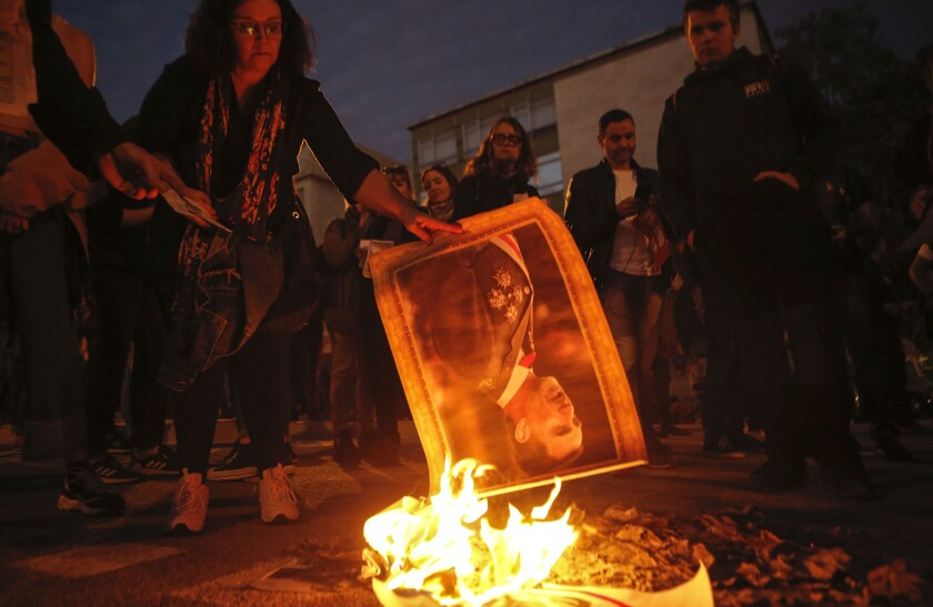 Protesters burn portraits of Spain's King Felipe during a protest outside the convention centre, as the Spanish Royal Family attends the Princess of Girona awards in Catalonia'a regional capital, Barcelona, Spain Monday, Nov. 4, 2019. (AP Photo/Joan Mateu)