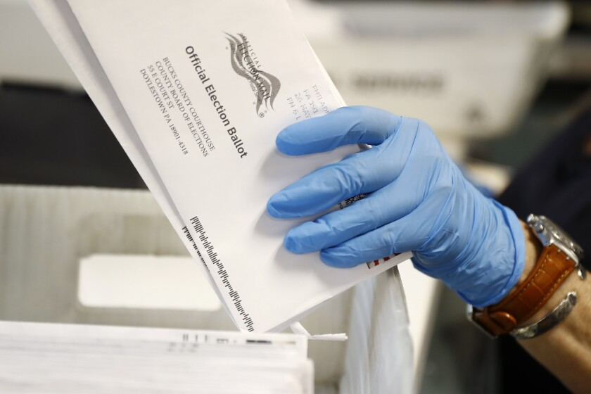 A worker holds a mail-in ballot envelope at the Bucks County Board of Elections office in Doylestown, Pa., in May.