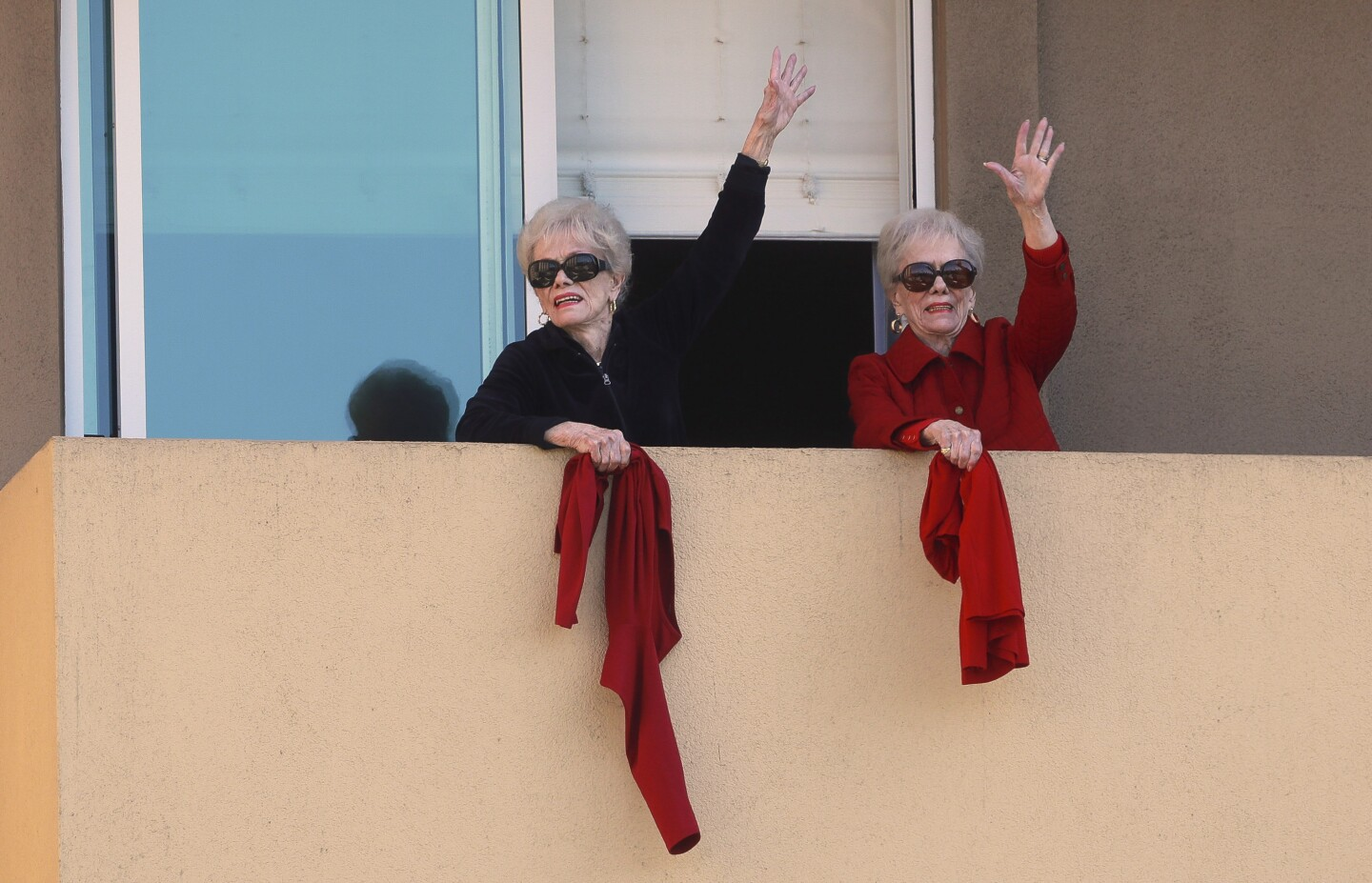 Joyce Kriesmer, 91, right, and her twin sister Jackie Voskamp wave from their balcony at Vi at La Jolla Village as they and several other quarantined residents of the senior living apartment building gather on their balconies to participate in a daily afternoon pep rally on Wednesday, April 1, 2020 in San Diego, California.