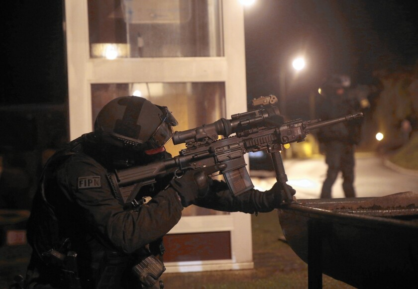 A member of the French police intervention force aids in a search in Fleury the day after the Charlie Hebdo attack.