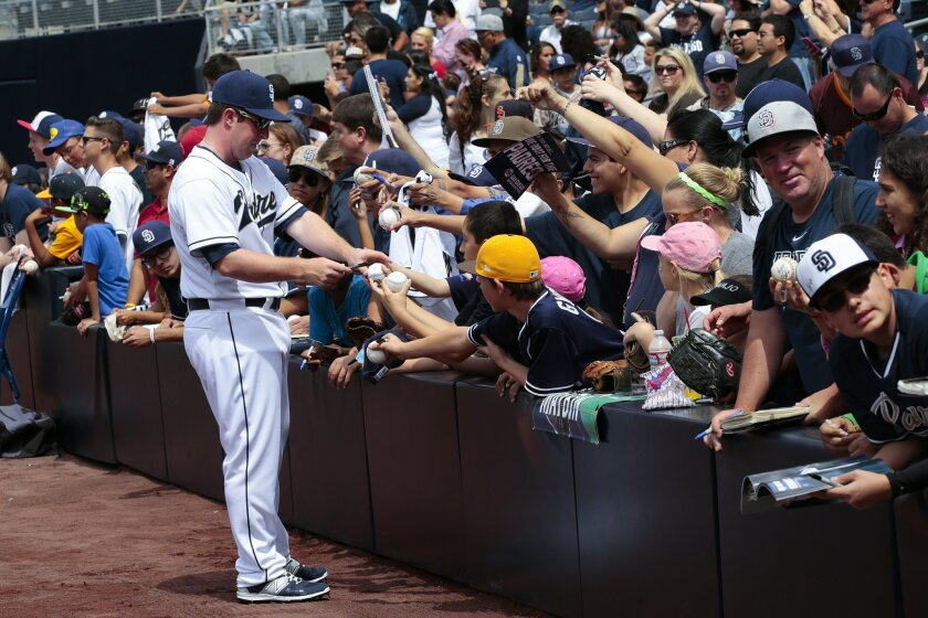 Padres fans hold out items to be autographed by Padres Jedd Gyorko during Fan Fest at Petco Park.
