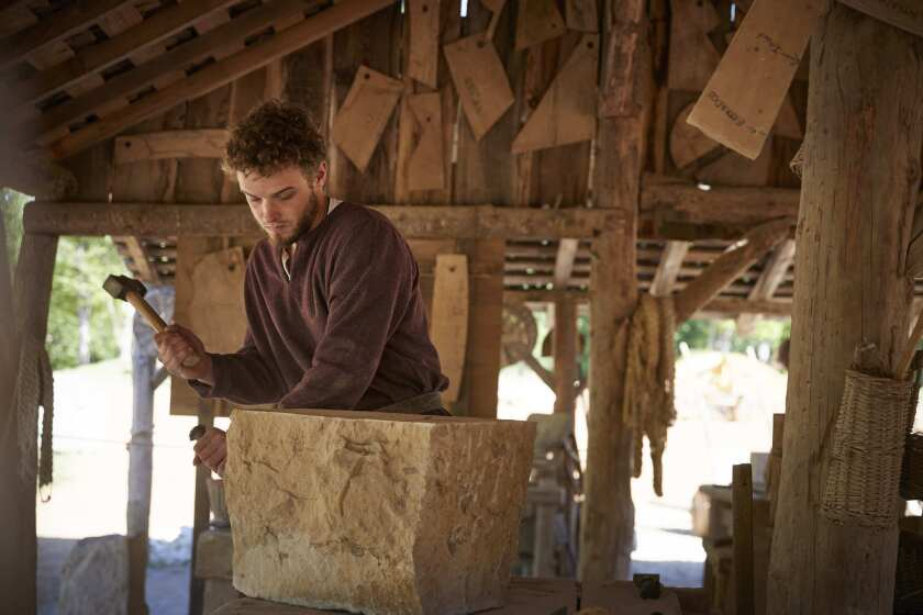 GUEDELON CASTLE, FRANCE - MAY 23: Stonemason Toendra Schrauwen, shapes a stone in the masonry worksh