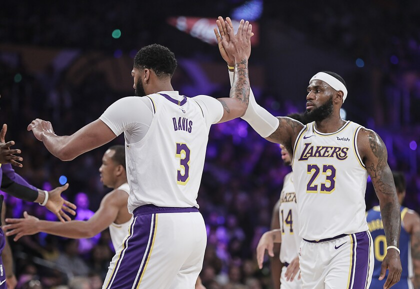 Lakers forwards Anthony Davis (3) and LeBron James (23) celebrate after a play during a preseason game against the Warriors.