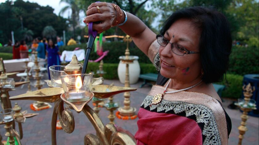 Lata kumar lights brass lamps at dusk for the 8th Annual Festival of Lights-Diwali Celebrations at Balboa Park Saturday.