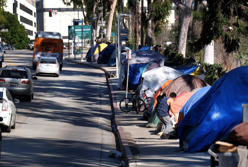 Tents from a homeless encampment line a street in downtown Los Angeles .