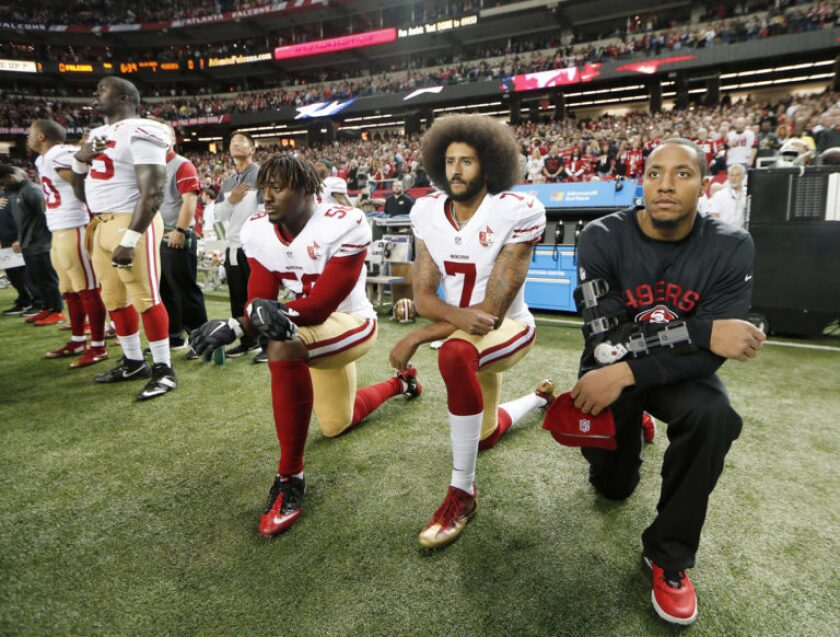 In this Dec. 18, 2016, file photo, San Francisco 49ers quarterback Colin Kaepernick (7) and outside linebacker Eli Harold (58) kneel during the playing of the national anthem before an NFL football game against the Atlanta Falcons in Atlanta.