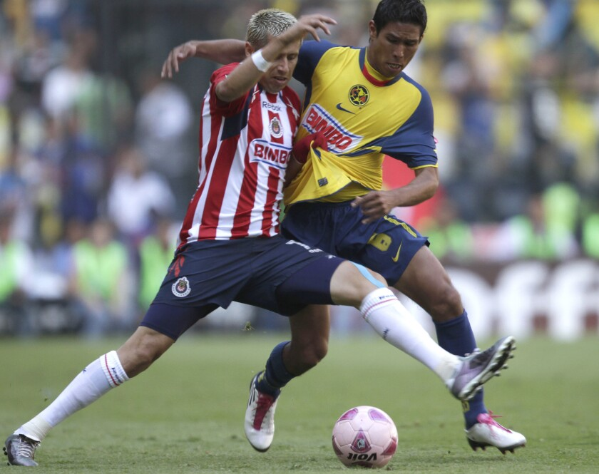 Chivas' Adolfo Bautista, left, fights for the ball with America's Juan Valenzuela during a Mexican soccer league game at the Azteca stadium in Mexico City, Sunday, Oct. 24, 2010. The game ended tied 0-0.
