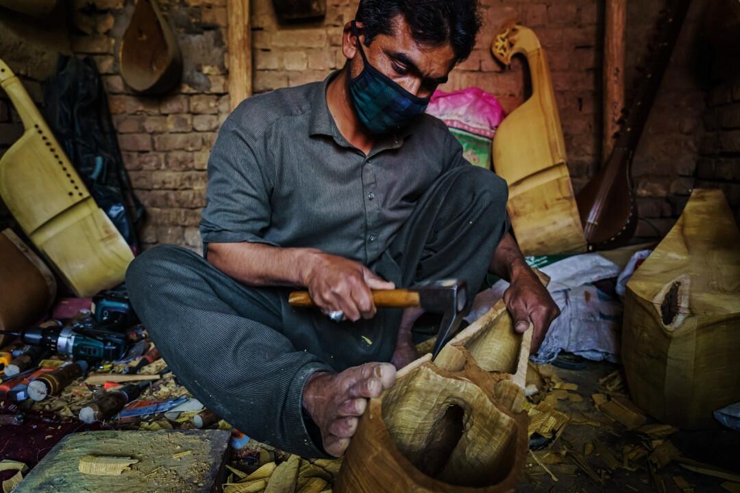 عزت الله نعمت یک بلوک چوبی تراش می دهد تا یک روباب سنتی افغانستان درست کند.