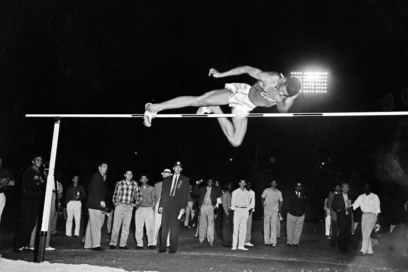 Charles Dumas soars to a world record with a leap over 7 feet during men's high jump competition.