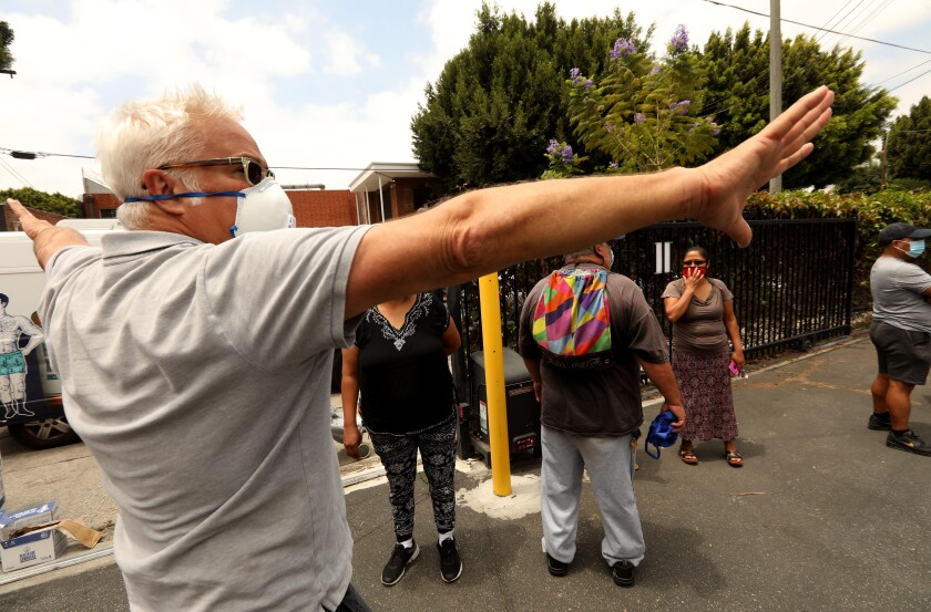 Craig Taubman directs people to wait in a line for a food giveaway for needy residents at the Pico Union Project.