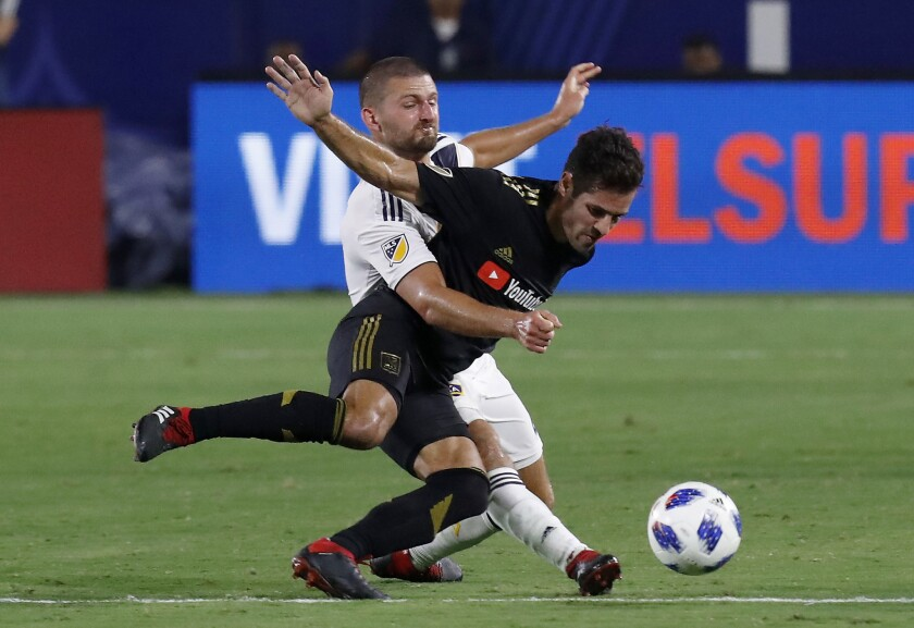 CARSON, CALIF. - AUG. 24, 2018. Galaxy midfielder Perry Kitchen gets tangled up with LAFC defender