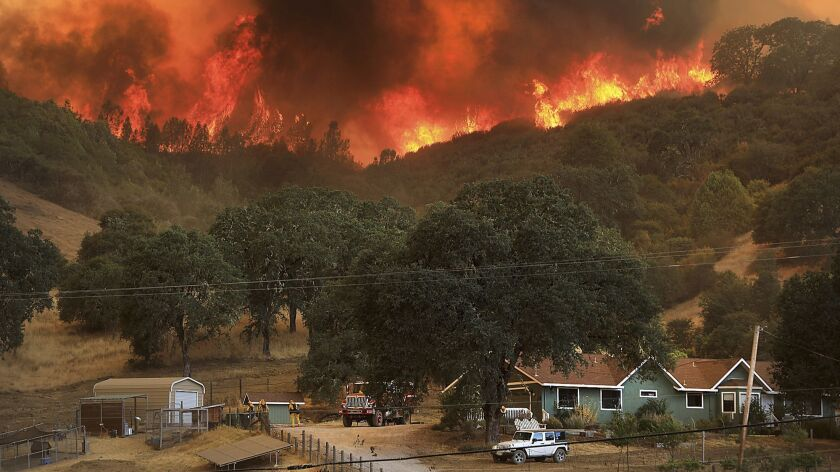 A wildfire towers over homes last week near Lakeport, Calif.