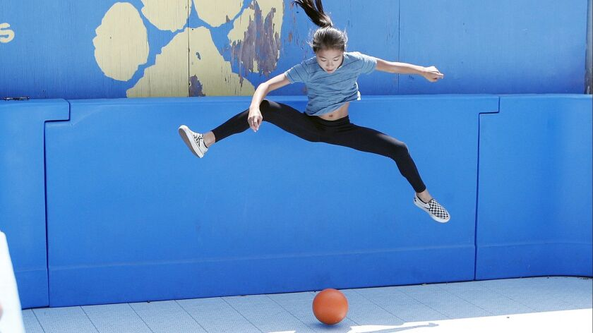 Sixth grader Naomi Hosford, 11, jumps really high to avoid being hit by the ball in a newly installe