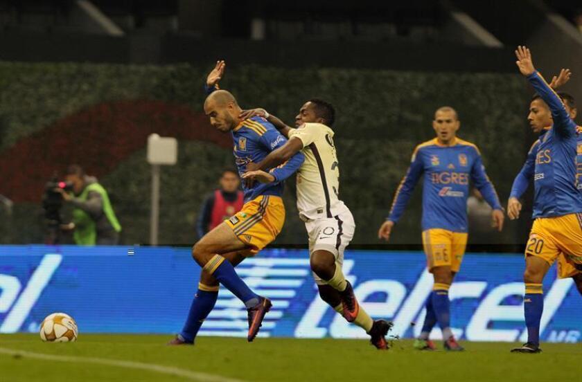 El jugador del América Alex Ibarra (i) disputa un balón con Guido Pizarro (d) de Tigres durante el partido de ida de la final del Torneo Apertura del fútbol mexicano, realizado en el Estadio Azteca, en Ciudad de México (México). EFE