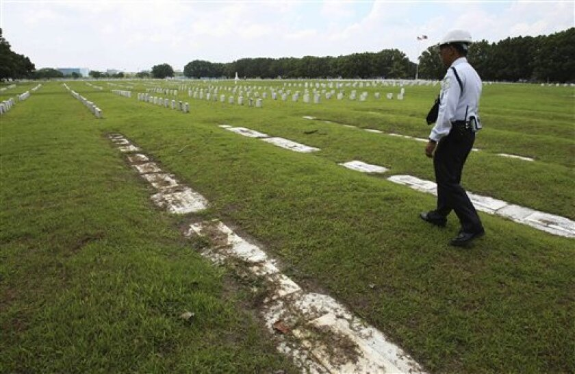 In this July 1, 2011 photo, a private guard walks along soil-covered grave markers at Clark Veterans Cemetery at the sprawling Clark Economic Zone, a former U.S. Air Force base in Dau, Pampanga province in northern Philippines. Retired U.S. soldiers, who voluntarily are keeping watch over the burial grounds, where some of their comrades lay, are waging a low-key battle to prod Washington to fund and take charge of the 2-acre (eight-hectare) cemetery. (AP Photo/Bullit Marquez)