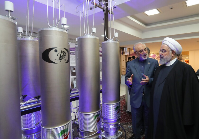 Iranian President Hassan Rouhani, right, listens to the head of Iran's nuclear technology organization, Ali Akbar Salehi.