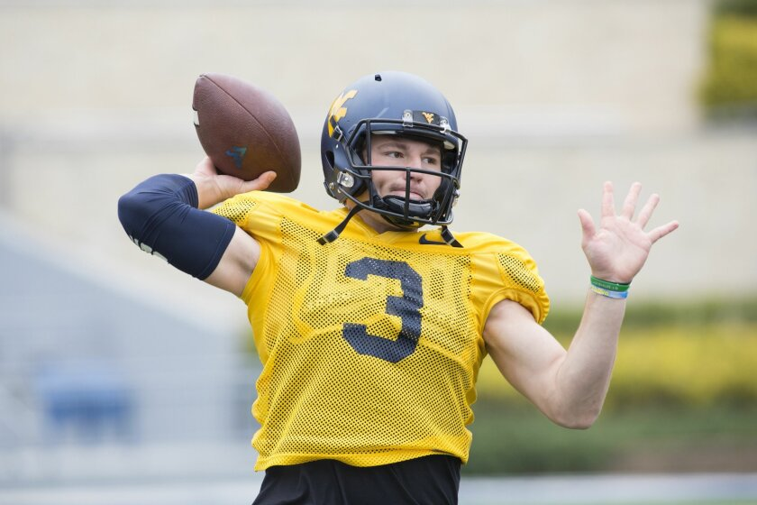 FILE - In this April 25, 2015, file photo, West Virginia quarterback Skyler Howard (3) makes a pass during a spring NCAA college football scrimmage in Morgantown, W.Va. Skyler Howard sees his promotion to starting quarterback at West Virginia as more than an opportunity to take over the offense. He wants to look like he knows what he's doing, and it starts with staying focused. (AP Photo/Raymond Thompson, File)