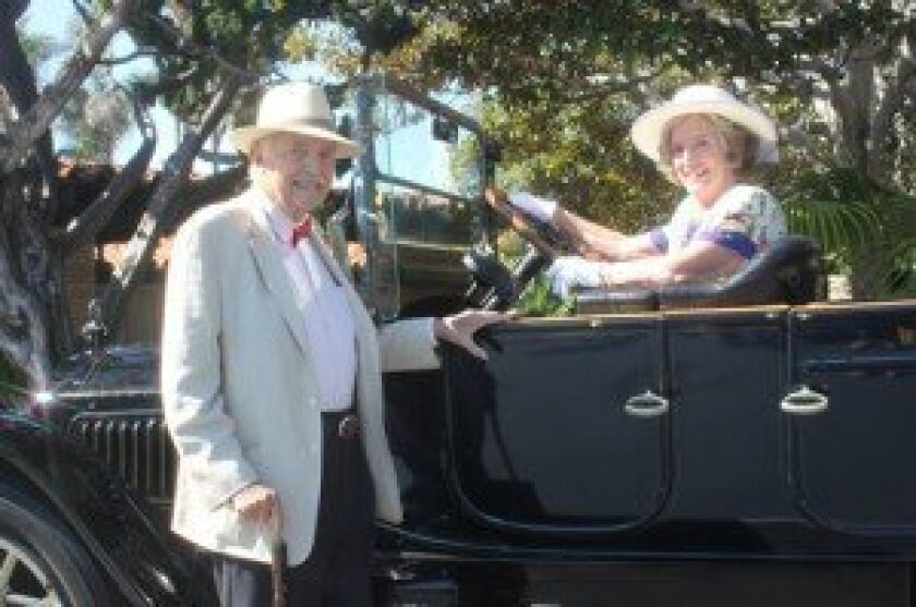lewis and connie Branscomb, event chair, pose with the 'Old Black Goose,' a 1915 Packard, on loan from the kellogg family as a backdrop for guest photos.