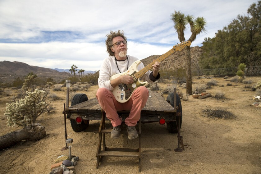 Joshua Tree musician Robbi Robb strums his Fender Stratocaster on an old trailer overlooking Joshua Tree landscape.