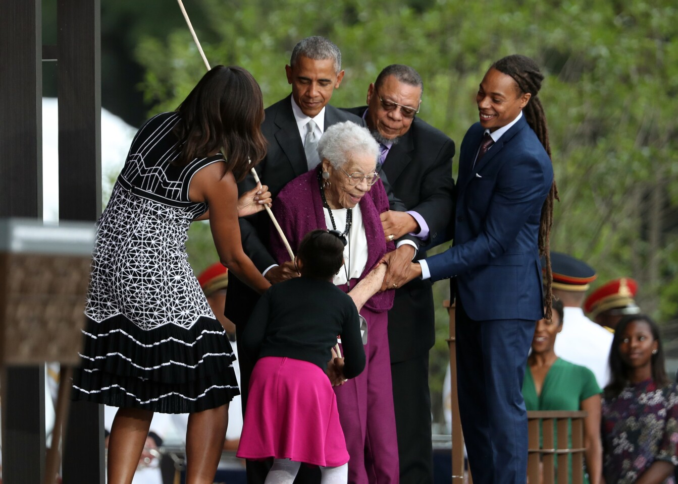 President Barack Obama, with first lady Michelle Obama and Ruth Odom Bonner, center, ring the bell opening the Smithsonian National Museum of African American History and Culture on the National Mall in Washington, Saturday, Sept. 24, 2016.