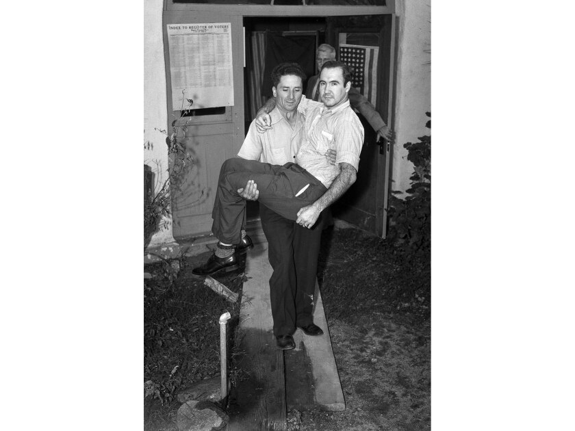Nov. 5, 1940: Walter Howard helped disabled World War I veteran Glenn Switzer get to the polls in Duarte.