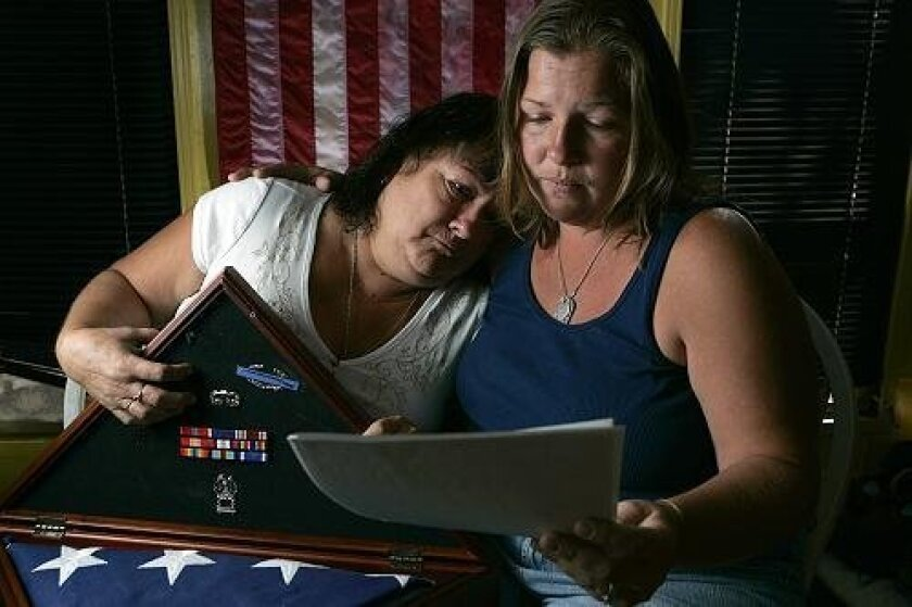 Alina Perez (right) read the report of how her brother, Sgt. Charles Wyckoff, was killed in action. She mourned with Wyckoff's mother, Sylvia. - NELVIN C. CEPEDA / Union-Tribune