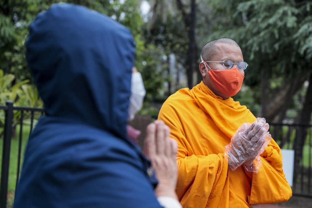 Groceries donated by Sadie Chen, left, receive a blessing at the Dhammakaya Temple-Peace Point Meditation Center in Azusa on Wednesday.