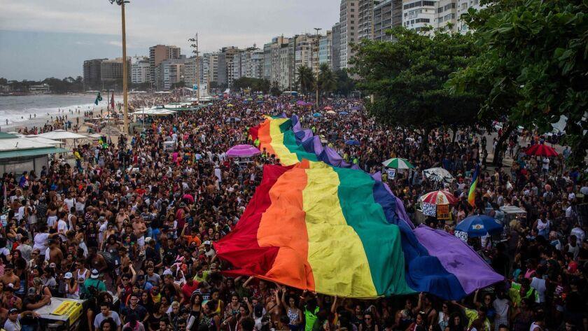 Participants hold up a giant rainbow flag during a gay pride parade at Copacabana Beach in Rio de Janeiro on Sept. 30.