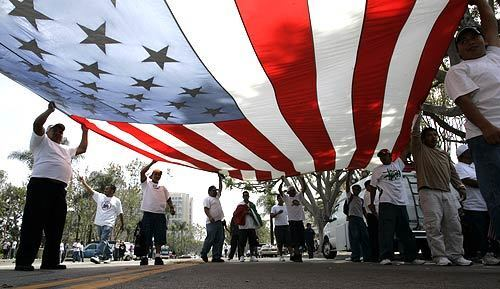 Marchers chant and carry a giant American flag down Ross Street in Santa Ana.