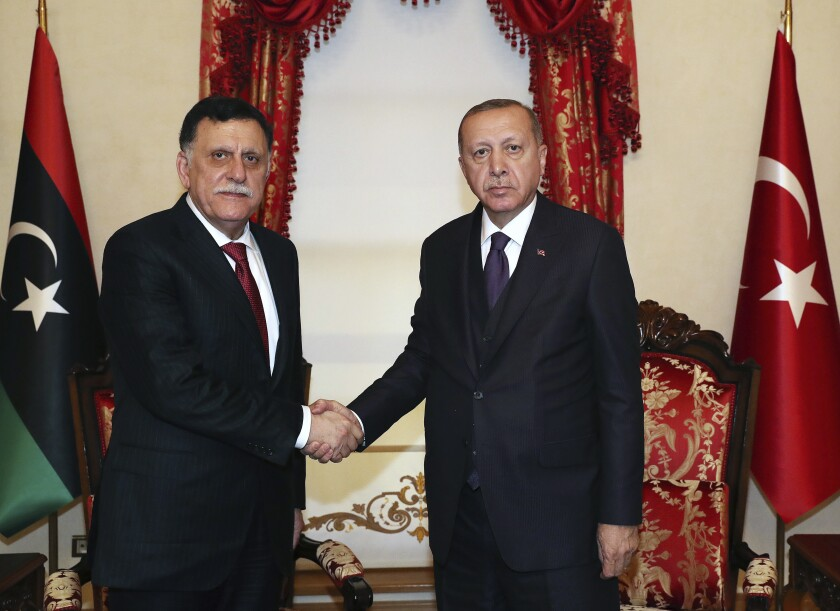 Turkey's President Recep Tayyip Erdogan, right, shakes hands with Fayez al Sarraj, the head of Libya's internationally recognised government, prior to their talks in Istanbul, Sunday, Dec. 15, 2019. Turkey and Libya had reached an agreement on the delineation of maritime boundaries in the Mediterranean, in November. (Turkish Presidency via AP, Pool)