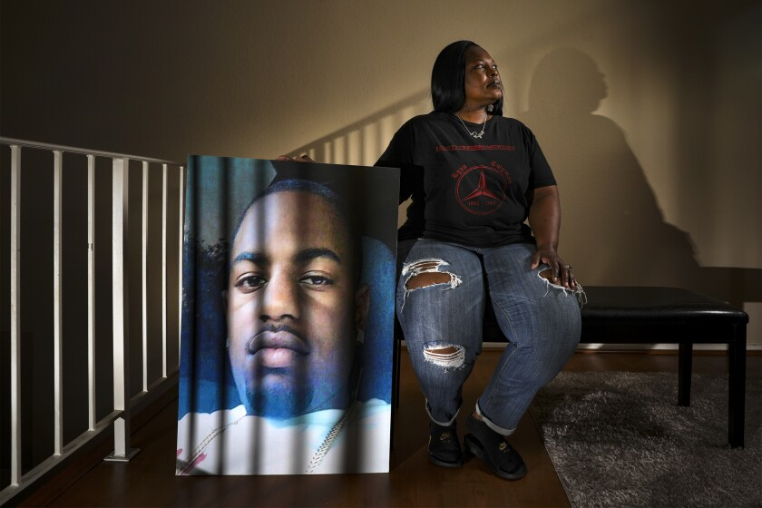 Tommy Twyman sits on a bench in her home, holding a large portrait of her son Ryan Twyman, who was killed by deputies