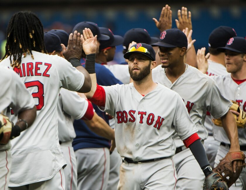 Boston Red Sox second baseman Dustin Pedroia, center, celebrates with teammates after defeating the Toronto Blue Jays during 11th inning baseball action in Toronto on Sunday, May 29, 2016. The Red Sox won, 5-3. (Nathan Denette/The Canadian Press via AP) MANDATORY CREDIT