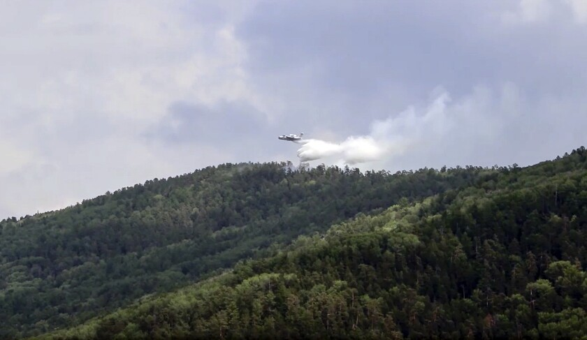 """FILE - In this Friday, July 10, 2020 file grab taken from video provided by Russian Emergency Ministry, shows a Russian Emergency Ministry's Beriev plane BE-200 Be-200 multipurpose amphibious aircraft releasing water in the Trans-Baikal National Park in Buryatia, southern Siberia, Russia. The U.N. weather agency is warning that average temperatures in Siberia came in 10 degrees Celsius (18 Fahrenheit) above average last month, a spate of exceptional heat that has fanned devastating fires in the Arctic Circle. The high heat has also contributed to the rapid depletion of ice sea coverage off the Russian Arctic coast. World Meteorological Organization Secretary-General Petteri Taalas said the Arctic is heating more than twice as fast as the global average. WMO says the extended heat is linked to a large """"blocking pressure system"""" and northward swing of the jet stream. (Russian Emergency Ministry Press Service via AP, File)"""