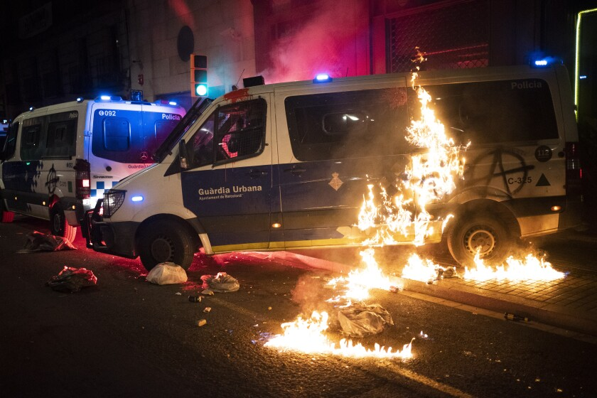 A police van is set on fire as protestors throw molotov cocktails at police during clashes following a protest condemning the arrest of rap singer Pablo Hasél in Barcelona, Spain, Saturday, Feb. 27, 2021. After a few days of calm, protests have again turned violent in Barcelona as supporters for a jailed Spanish rapper went back to the streets. (AP Photo/Emilio Morenatti)