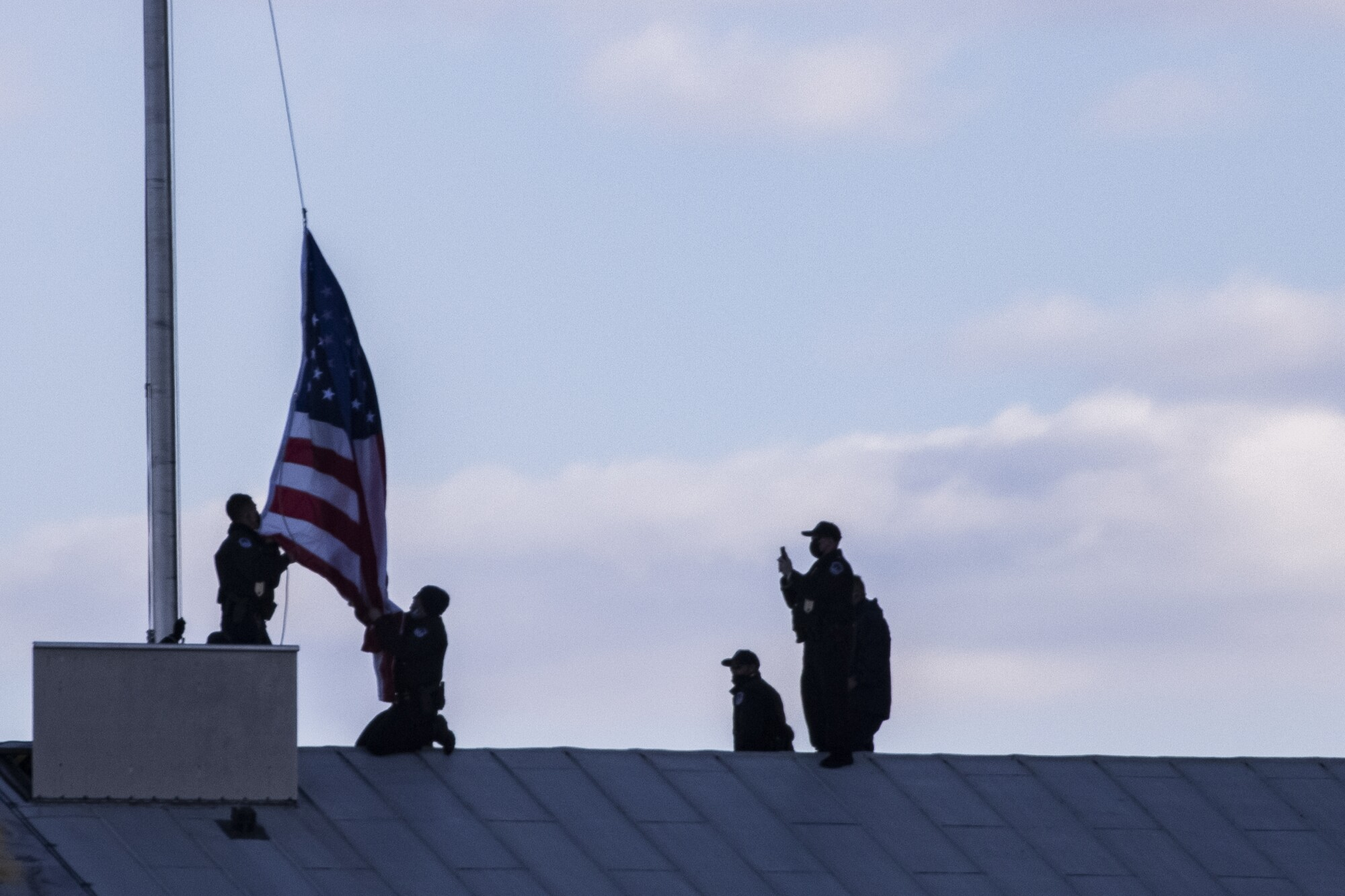 Capitol Police officers lower and replace the American flag to half staff over the U.S. Capitol