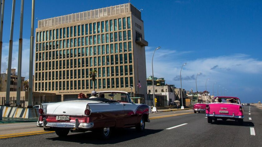 Tourists ride classic convertible cars on the Malecon past the U.S. Embassy in Havana.