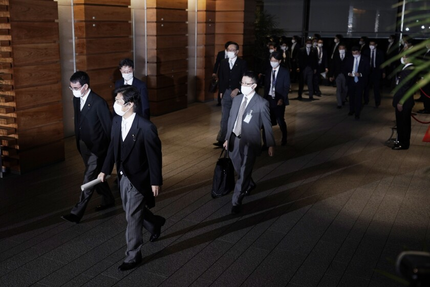 Newly appointed ministers, left, are escorted by staffs as they leave the official residence for the Imperial Palace to attend the attestation ceremony of the new cabinet by Prime Minister-elect Yoshihide Suga, Wednesday, Sept. 16, 2020, in Tokyo. (AP Photo/Eugene Hoshiko)