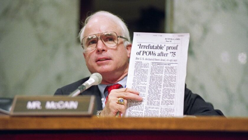 Sen. John McCain (R-Ariz.) holds up an article from the Washington Times during a hearing of the Senate Select Committee on POW/MIA Affairs on Capitol Hill in Washington in June 1992.