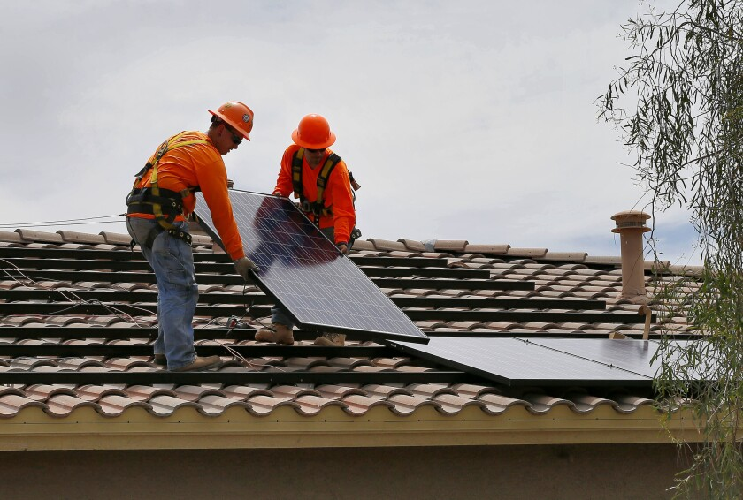 FILE - In this July 28, 2015, file photo, electricians, Adam Hall, right, and Steven Gabert install solar panels on a roof for Arizona Public Service company in Goodyear, Ariz. As states across the U.S. West beef up their renewable energy mandates, a push to do so in Arizona has been met by fierce resistance from the Republican governor and GOP-dominated Legislature. (AP Photo/Matt York, File)