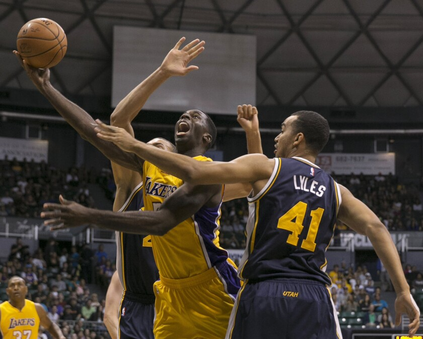 Lakers forward Brandon Bass goes up for a layup between Jazz forward Trey Lyles and center Rudy Gobert during the first half of Tuesday's preseason game.