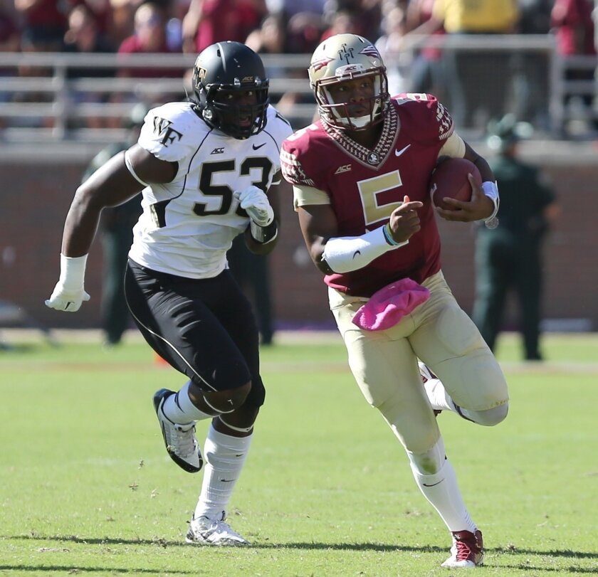 Florida State's Jameis Winston runs from the pursuit of Wake Forest's Duke Ejiofor in the second quarter an NCAA college football game, Saturday, Oct. 4, 2014 in Tallahassee, Fla. Florida State won the game 43-3. (AP Photo/Steve Cannon)