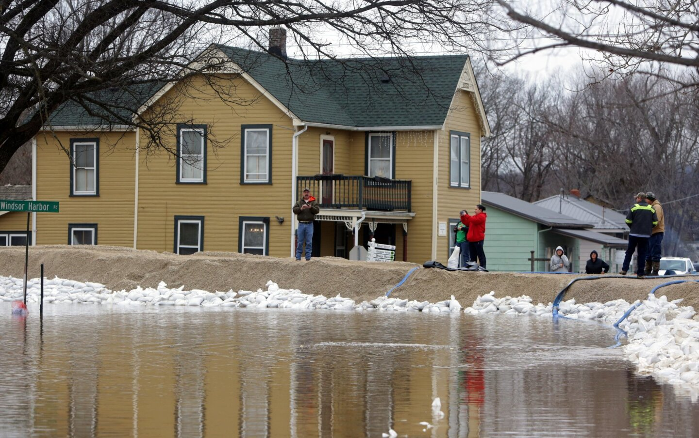 People hang out by the recently built-up levees holding rising Mississippi River waters at bay in Kimmswick, Mo., on Dec. 31, 2015.