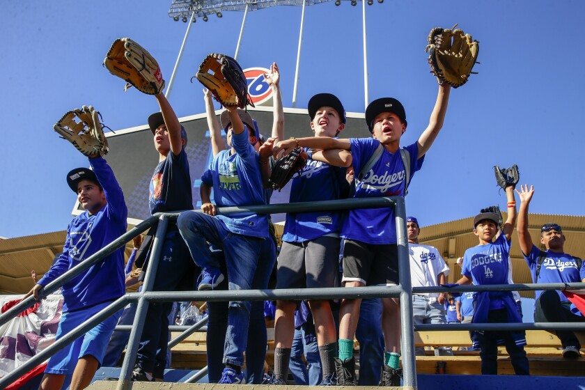 Young Dodgers fans look for a ball before Game 1 of the National League Division Series between the Dodgers and Washington Nationals in October.