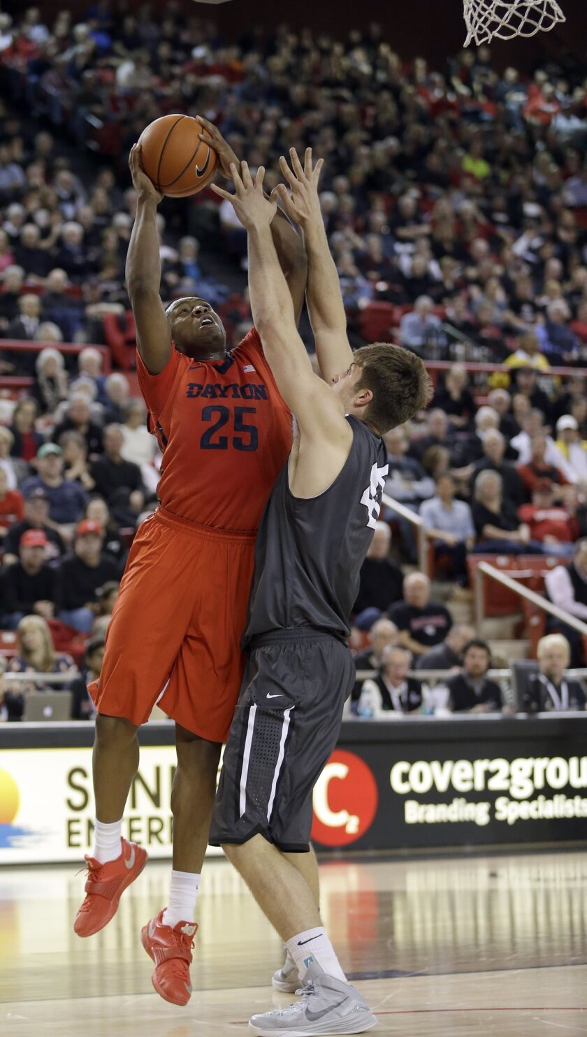 Dayton's Kendall Pollard, left, tries to get a shot off over Davidson's Andrew McAuliffe during the first half of an NCAA college basketball game in Davidson, N.C., Tuesday, Jan. 20, 2015. (AP Photo/Bob Leverone)
