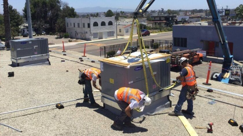 A team installs an heating, ventilation and air conditioning system at one of the Sweetwater Union High School District schools.