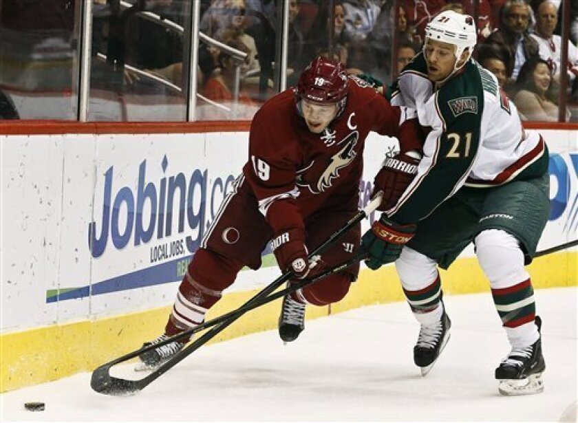 Phoenix Coyotes' Shane Doan (19) and Minnesota Wild's Kyle Brodziak (21) battle for the puck during the first period in an NHL hockey game, Thursday, Feb. 28, 2013, in Glendale, Ariz. (AP Photo/Ross D. Franklin)