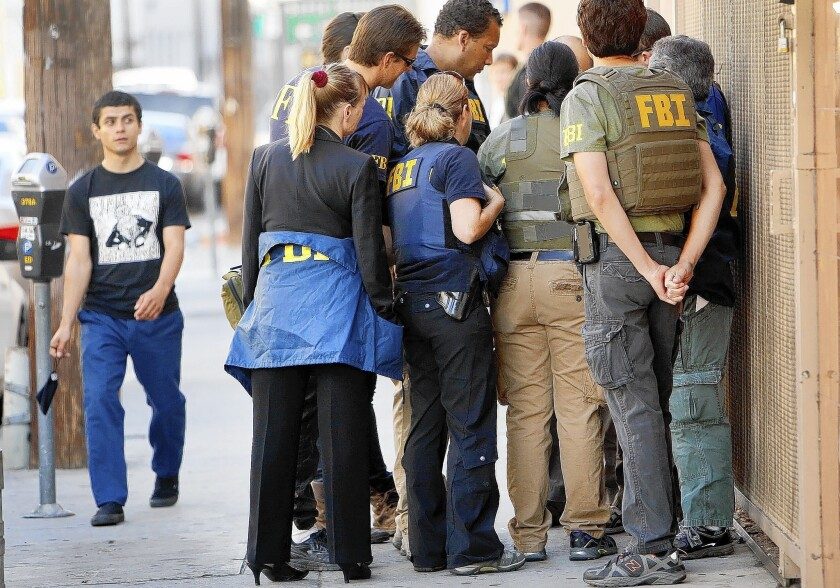 Federal agents huddle in the 700 block of East Pico Boulevard during a series of raids in the downtown L.A. fashion district. Nine people were arrested.