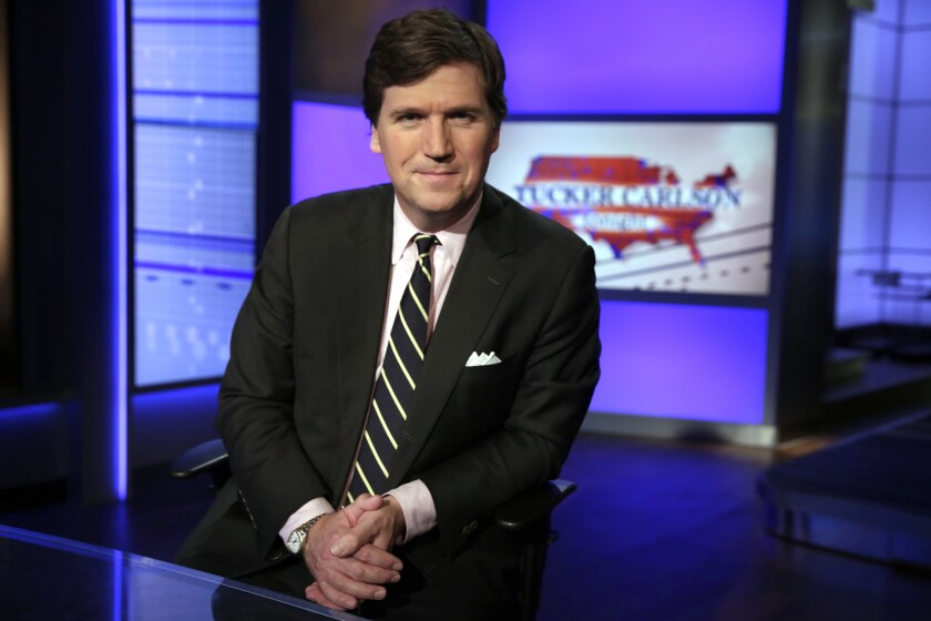 """FILE - In this Thursday, March 2, 2107 file photo, Tucker Carlson, host of """"Tucker Carlson Tonight,"""" poses for a photo in a Fox News Channel studio in New York. The Anti-Defamation League has called for Fox News to fire prime-time opinion host Tucker Carlson because he defended a white-supremacist theory that says whites are being """"replaced"""" by people of color. In a letter to Fox News CEO Suzanne Scott on Friday, April 9, 2021the head of the ADL, Jonathan Greenblatt, said Carlson's """"rhetoric was not just a dog whistle to racists — it was a bullhorn."""" (AP Photo/Richard Drew, File)"""