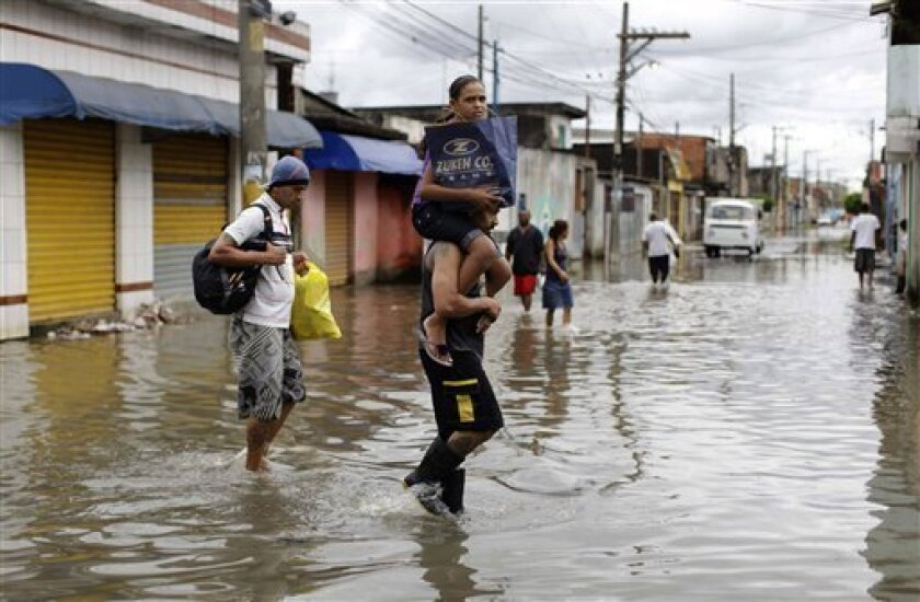 Residents, one carrying a girl on his shoulders, walk on a flooded street at Vila Itaim neighborhood in Sao Paulo, Brazil, Tuesday, Jan. 11, 2011. Brazilian authorities say heavy rains have triggered mudslides and floods in southeastern Brazil, killing at least 13 people. Sao Paulo state civil defense officials say 11 people died when their houses collapsed because of mudslides and two were killed in flash floods. (AP Photo/Nelson Antoine)